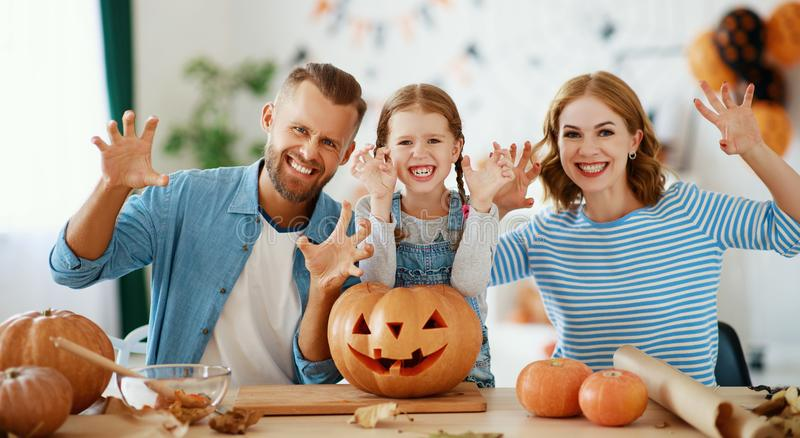 Happy  family mother father and child daughter prepare for Halloween decorate  home with pumpkins,  laughing and  play royalty free stock photography