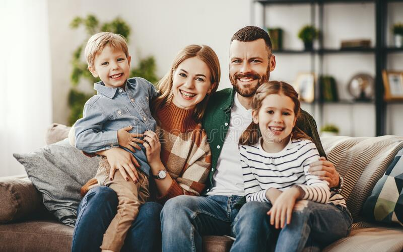 Happy family mother father and kids at home on couch royalty free stock image