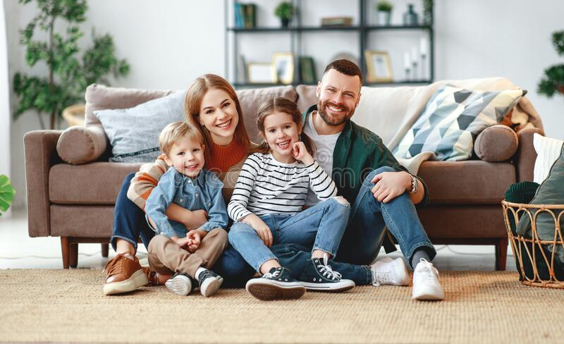 Happy family mother father and kids at home on couch royalty free stock images