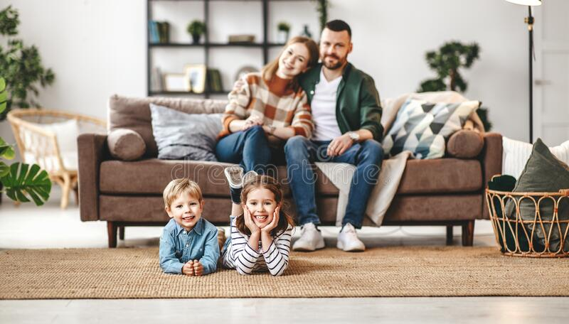 Happy family mother father and kids at home on couch stock images