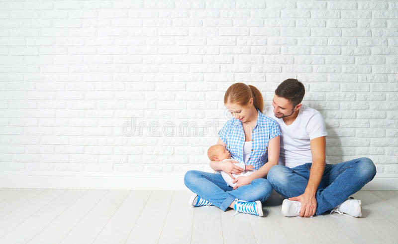 happy family mother, father of a newborn baby on floor near blank wall royalty free stock image