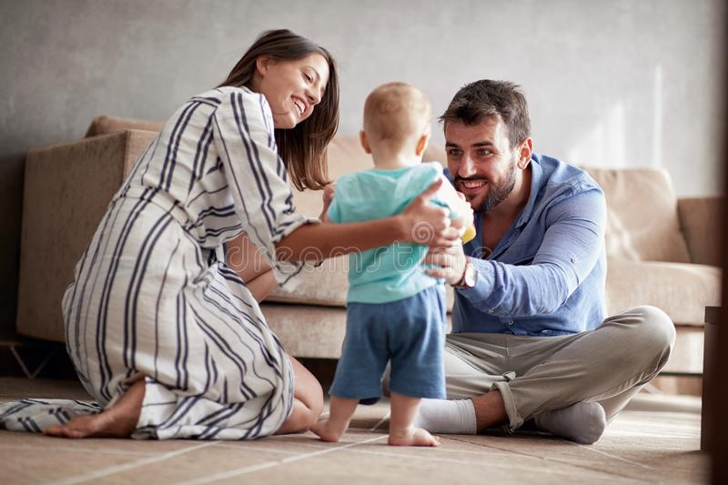 Happy family - mother and father playing with a baby at home royalty free stock images