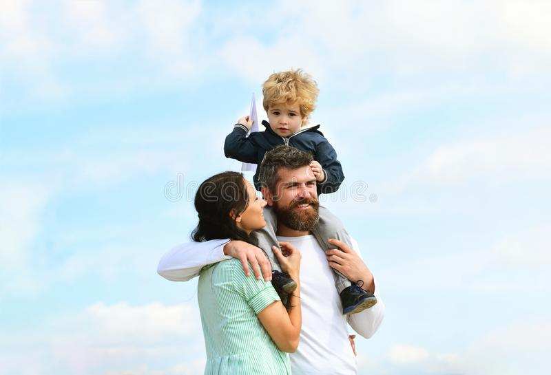 Happy family - mother, father and son on sky background in summer. Father and son building together a paper airplane stock image
