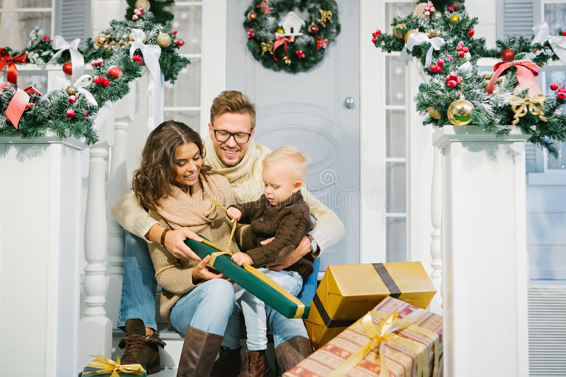 Happy family - mother, father and son unpack the Christmas gifts stock photo