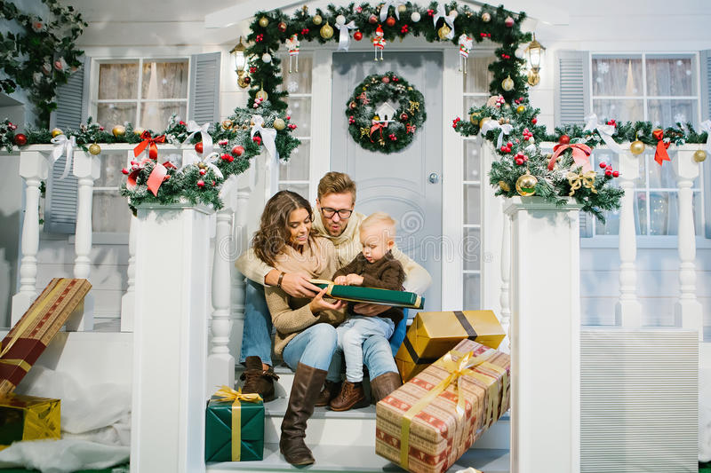 Happy family - mother, father and son unpack the Christmas gifts royalty free stock photography
