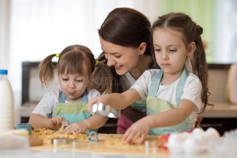 Happy family mother and kids are preparing the dough, bake cookies in the kitchen stock photo