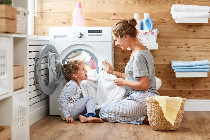Happy family mother housewife and child in laundry with washin. Happy family mother housewife and child daughter in laundry with washing machine stock photos