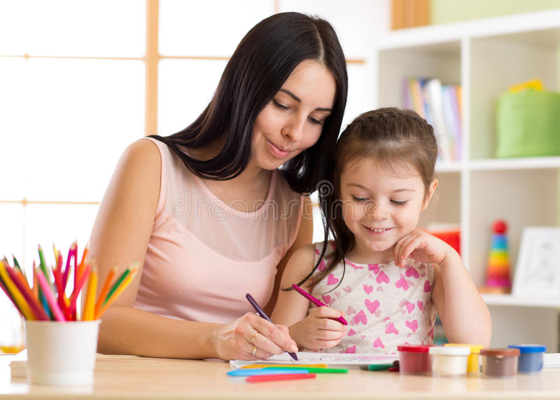 Happy family mother and kid daughter together paint. Woman helps child girl. royalty free stock image