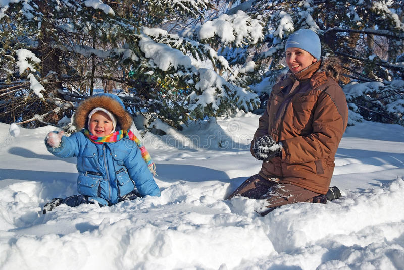 Happy family of mother with kid playing in the snow park royalty free stock images