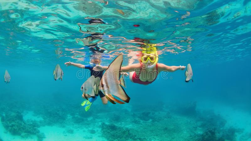 Mother, kid in snorkeling mask dive underwater with tropical fishes. Happy family - mother, kid in snorkeling mask dive underwater, explore tropical fishes royalty free stock photo