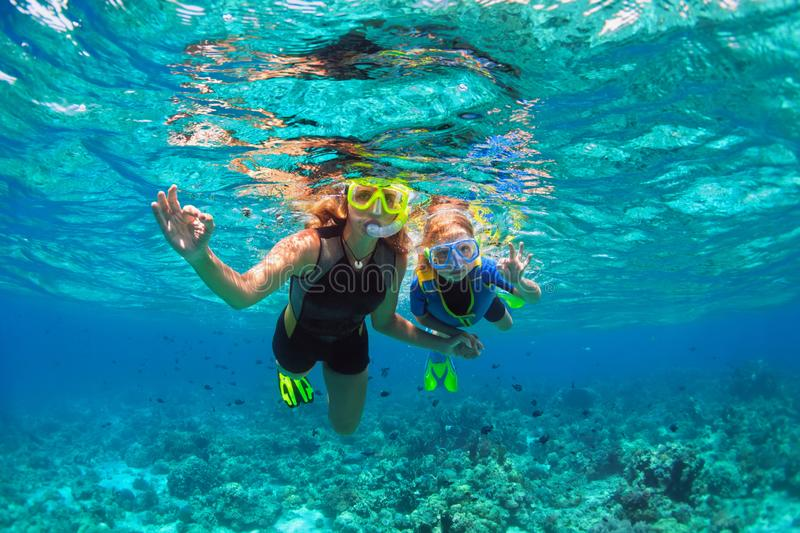Mother, kid in snorkeling mask dive underwater with tropical fishes. Happy family - mother, kid in snorkeling mask dive underwater with tropical fishes in coral royalty free stock photography