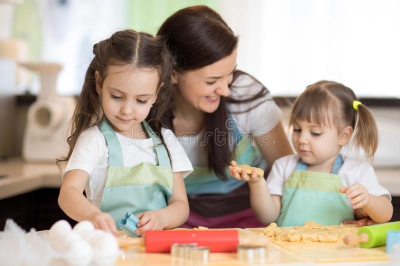Happy family mother and daughters are preparing bakery together. Mom and children are cooking cookies and having fun in royalty free stock photos