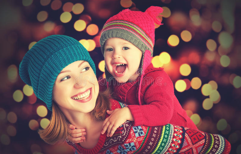 Happy family mother and little daughter playing in the winter for Christmas. Happy family mother and baby little daughter playing in the winter for the Christmas stock image
