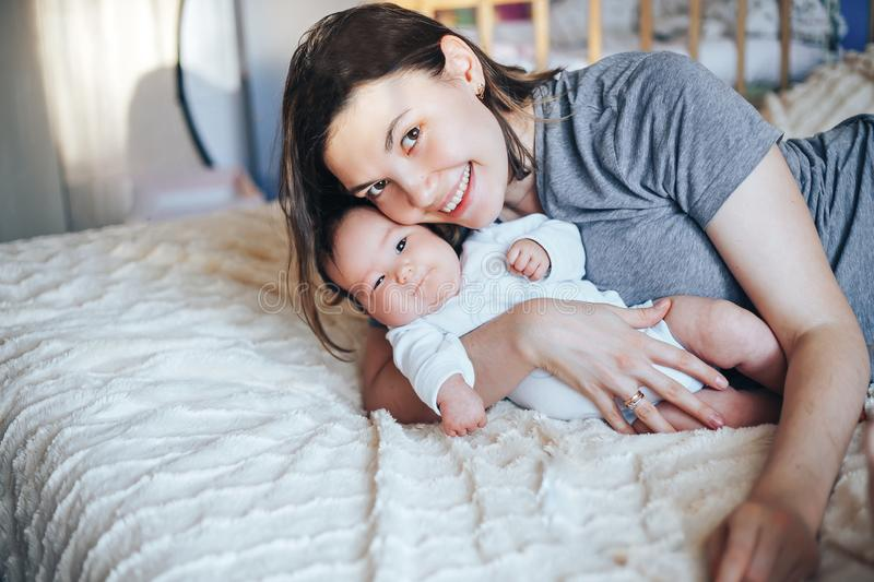 Smiling young woman with book and baby on a bed stock image