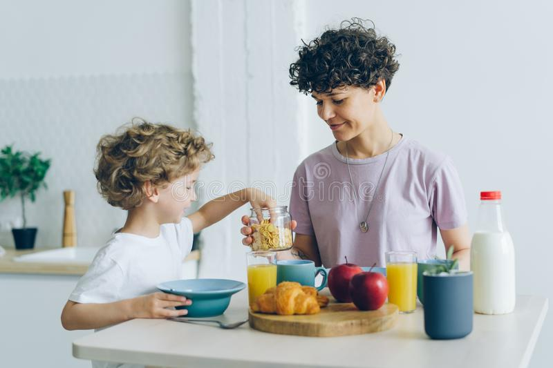 Happy family mother and son eating cereal with milk at home talking royalty free stock photography