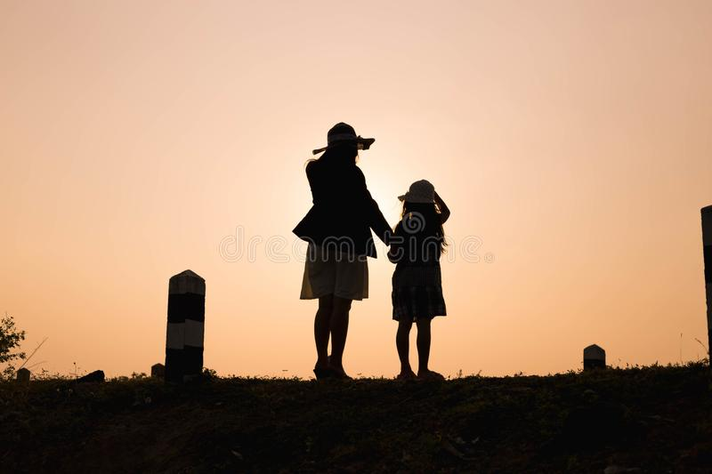 Happy family. A mother and son playing in grass fields outdoors at evening silhouette.Vintage Tone and copy space royalty free stock images
