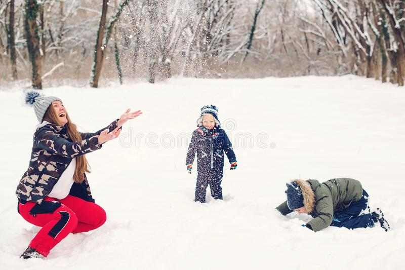 Happy family mother and sons having fun, playing with snow at winter walk outdoors. Happy christmas holidays. Winter snowy weather royalty free stock photo