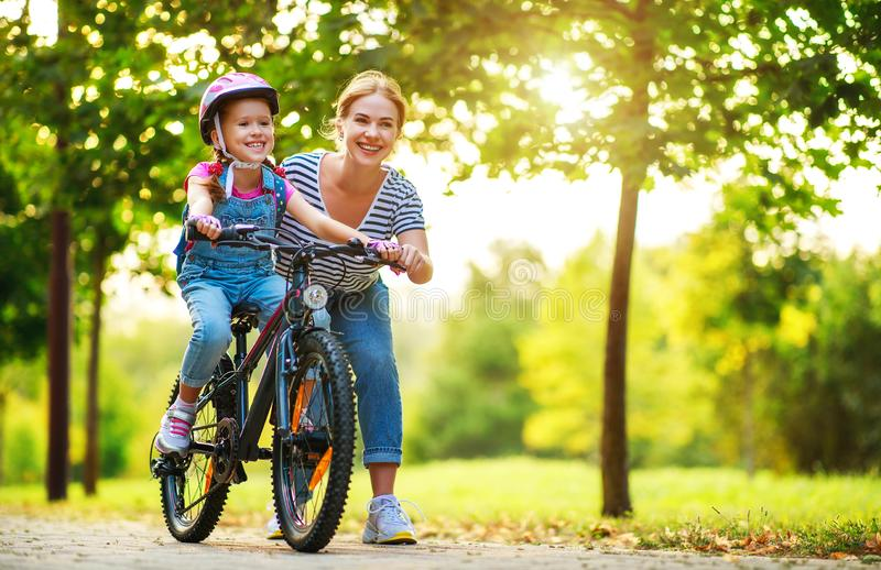 Happy family mother teaches child daughter to ride a bike in the Park. In nature stock photography