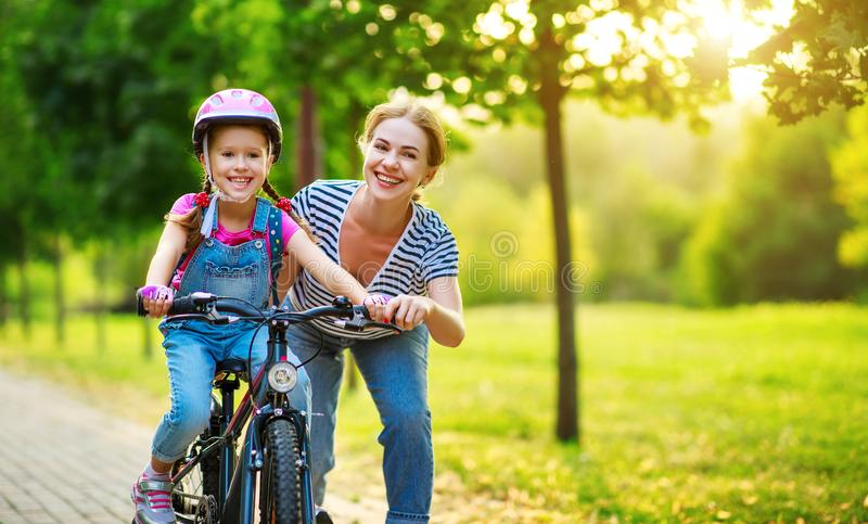 Happy family mother teaches child daughter to ride a bike in the Park stock photos