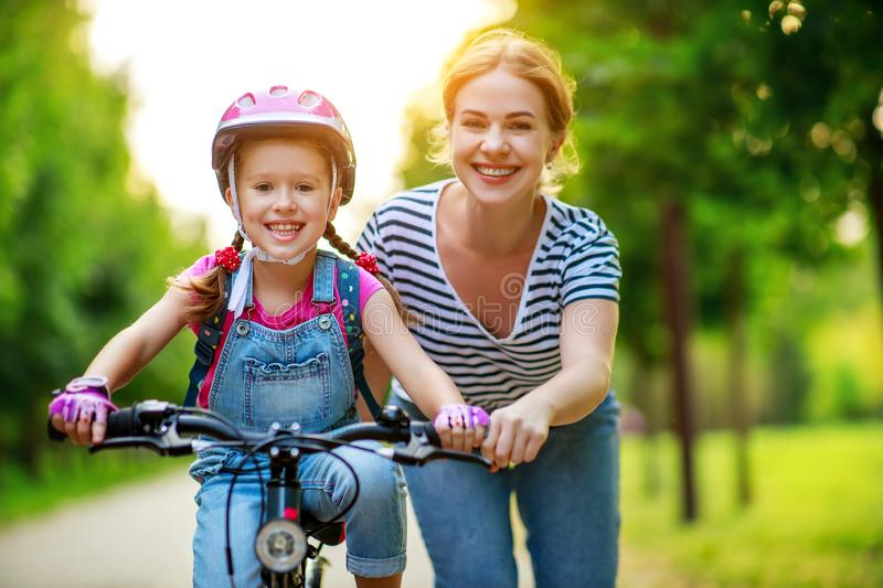 Happy family mother teaches child daughter to ride a bike in the Park royalty free stock photography