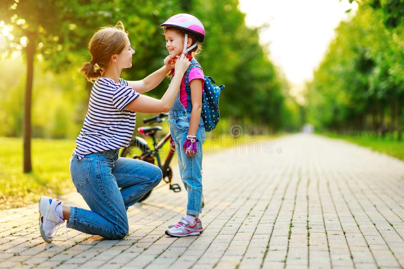 Happy family mother teaches child daughter to ride a bike in the Park royalty free stock image