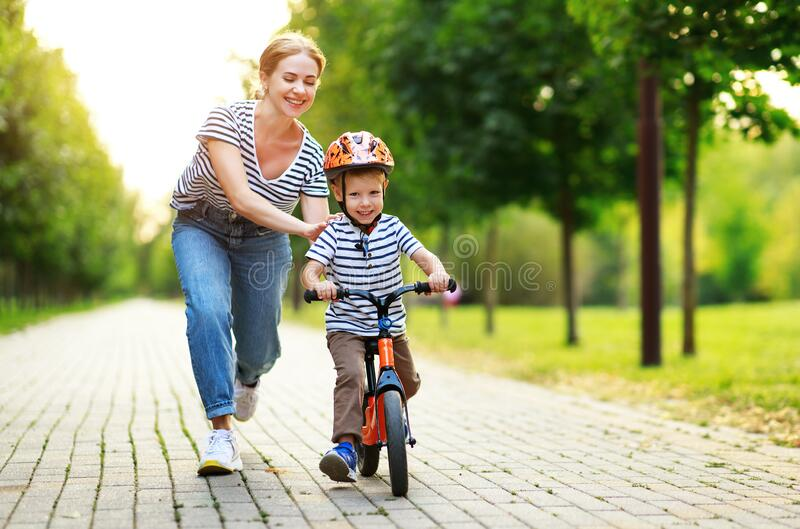 Happy family mother teaches child son to ride a bike in the Park royalty free stock images