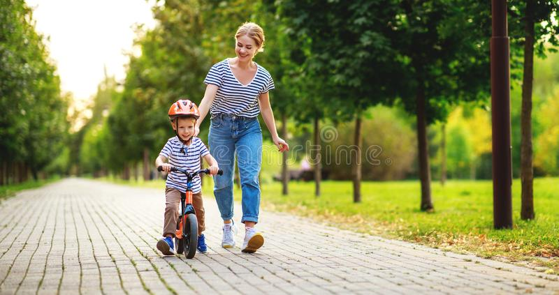 Happy family mother teaches child son to ride a bike in the Park. In nature stock image
