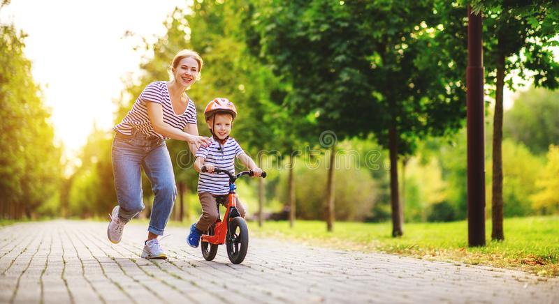 Happy family mother teaches child son to ride a bike in the Park. In nature royalty free stock photos
