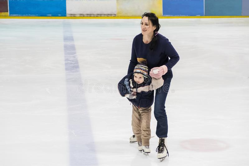 Happy family, mother teaches son ice skating at rink. Winter activities royalty free stock image