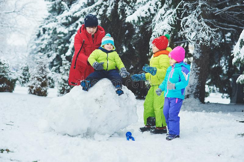 a happy family. mother and three children playing in the winter forest. stock photo