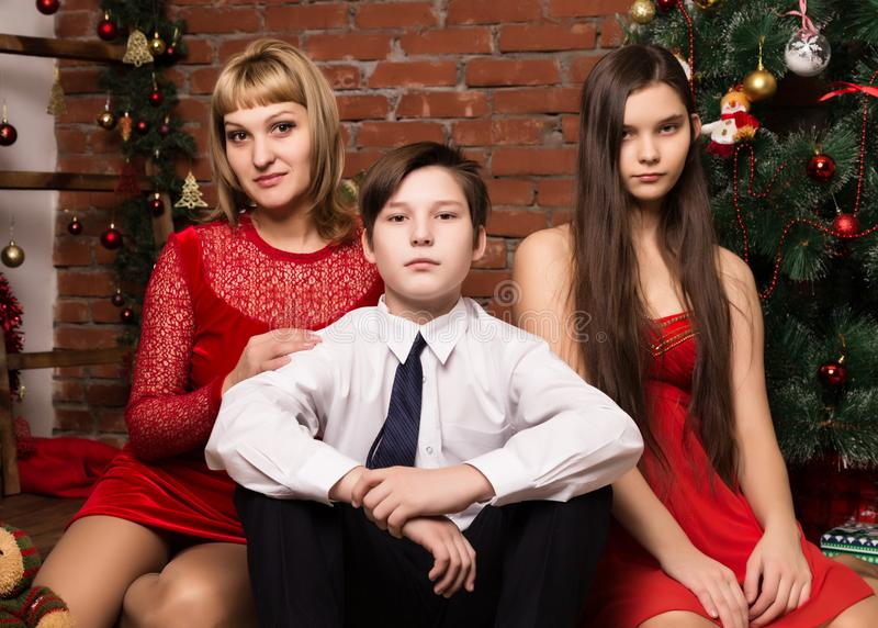 Happy family, mother with two children next to cristmas tree in Christmas day royalty free stock images