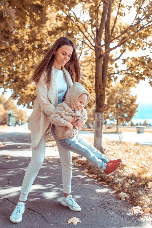 Happy family, mother woman little boy 4-5 years old, playing having fun, laughing park, background trees foliage. Warm royalty free stock image