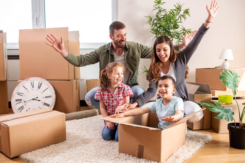 Happy family moving in their new home and having a playtime with their children royalty free stock image