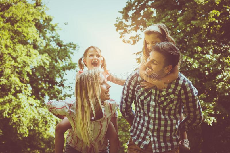 Happy family in nature. Parents carrying their daughter on piggy royalty free stock images