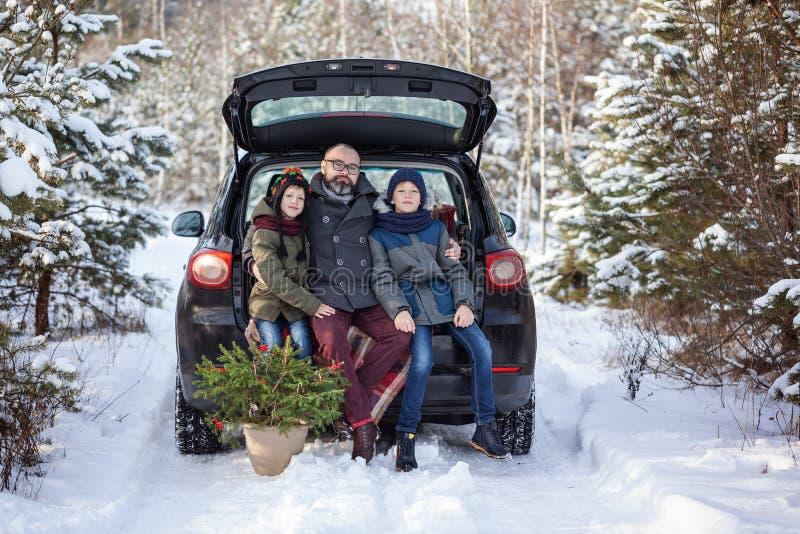 Happy family near black car at snowly winter day. Concept holiday vacation royalty free stock photos