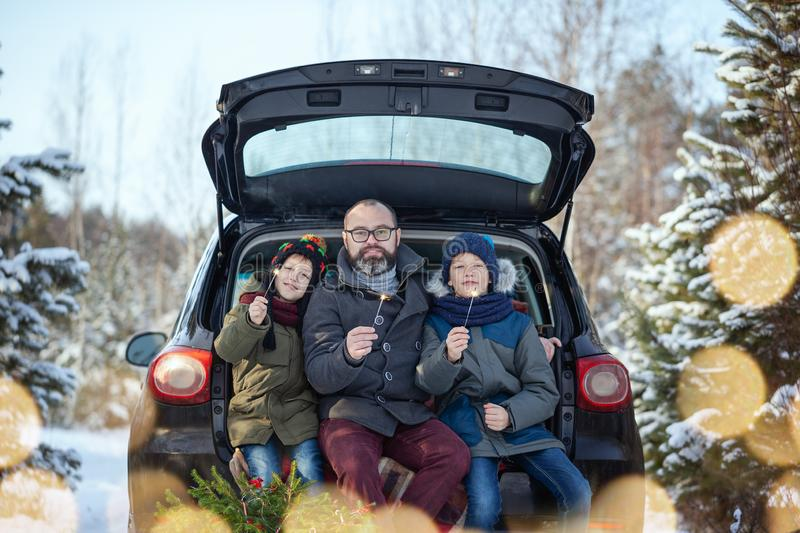Happy family near black car at snowly winter day. Concept holiday vacation royalty free stock images
