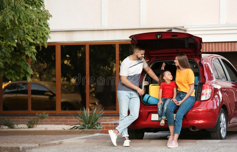 Happy family near car with open trunk royalty free stock photography