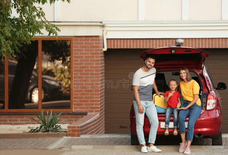 Happy family near car with open trunk royalty free stock images