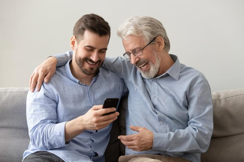 Happy family old father embracing young son enjoying using smartphone. Happy two age generations men family old father embracing young grown adult son having fun royalty free stock photo