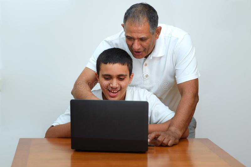 Happy family old grandfather and grandson on laptop.Elderly teacher trainer and teen pupil boy. stock photo