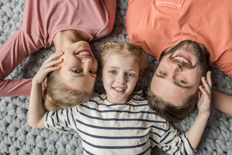 Happy family with one child lying together on grey knitted carpet royalty free stock photo