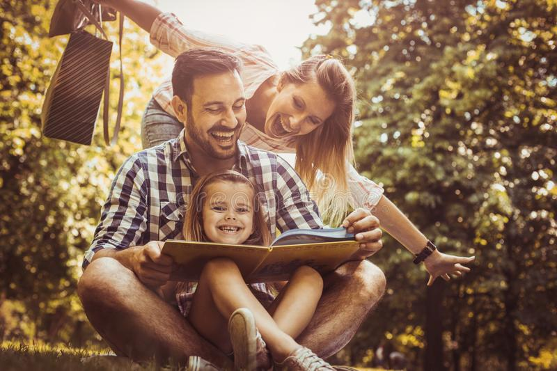 Happy family with one child in meadow reading book together. royalty free stock images