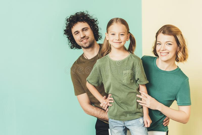 happy family with one child wearing t-shirts and smiling stock photos