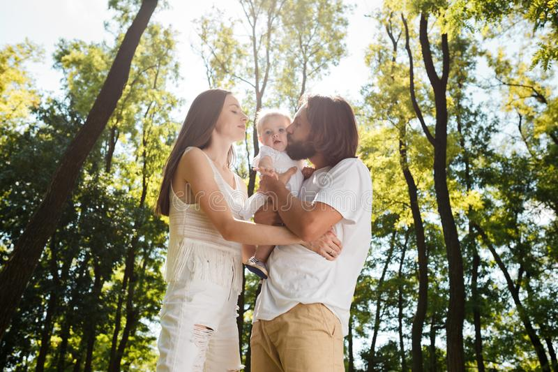 Happy family on the open air. Young dark-haired woman and her husband are kissing their charming little daughter. stock photos
