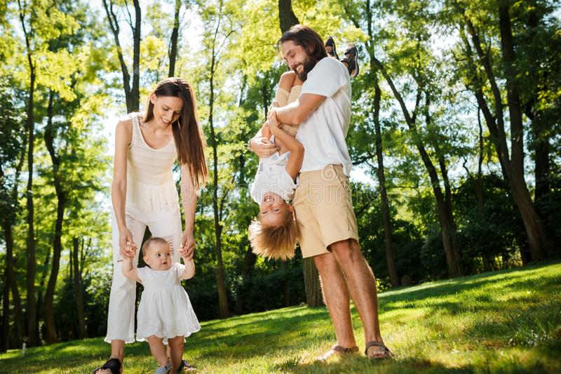 Happy family on the open air. Young dark-haired woman walking with her little daughter and her husband playing with son. royalty free stock photos