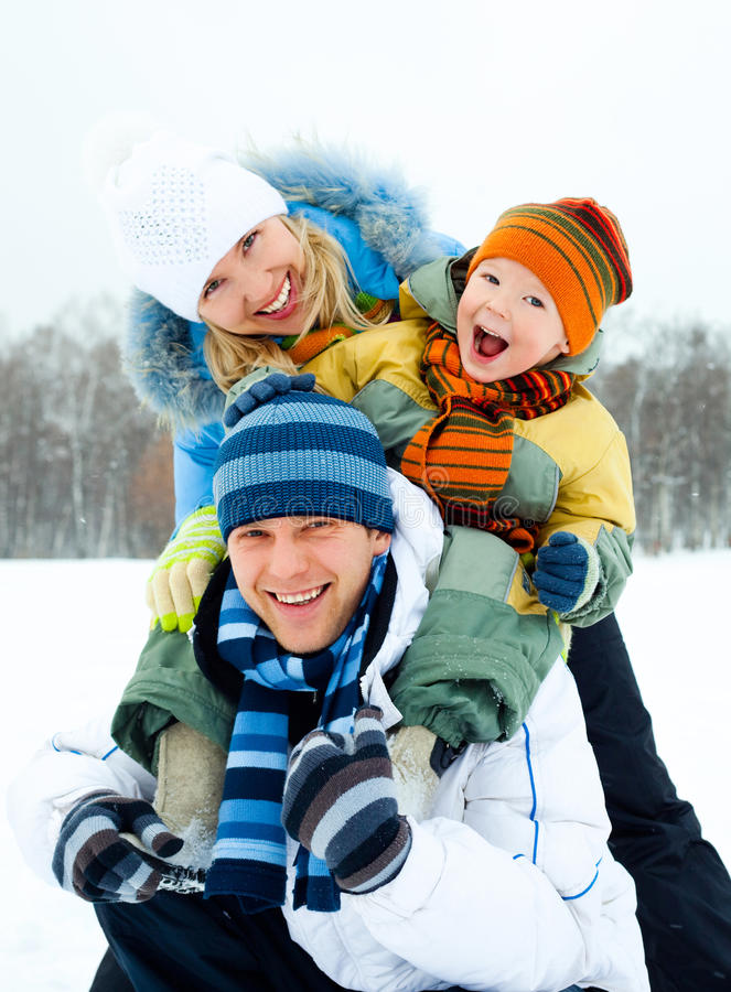 Happy family outdoor. Happy young family spending time outdoor in winter park stock image