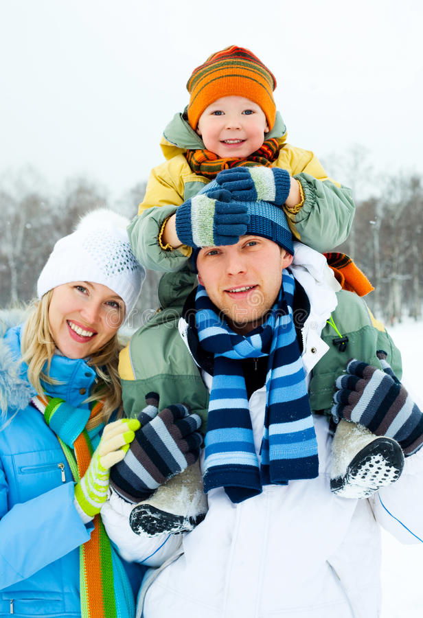 Happy family outdoor. Happy young family spending time outdoor in winter park (focus on the man royalty free stock image