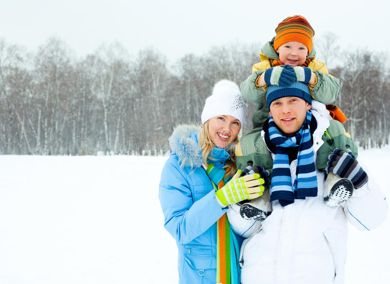 Happy family outdoor. Happy young family spending time outdoor in winter park (focus on the man royalty free stock photo