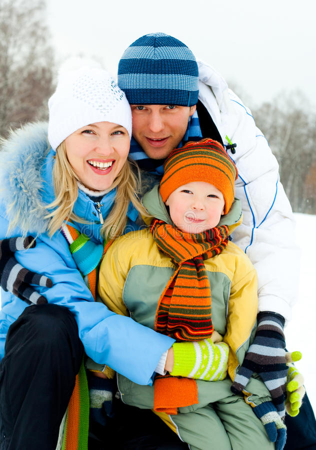 Happy family outdoor. Happy young family spending time outdoor in winter park royalty free stock image
