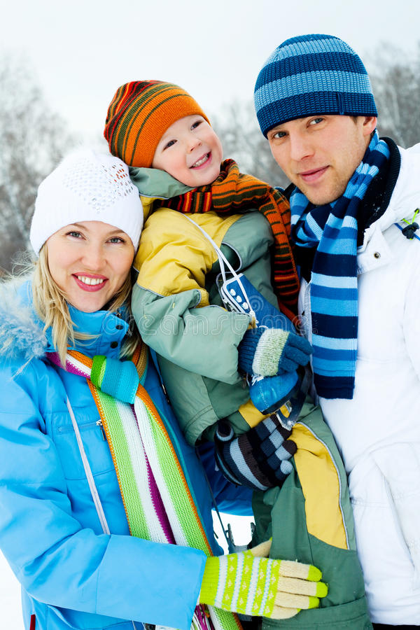 Happy family outdoor. Happy young family spending time outdoor in winter park royalty free stock photography
